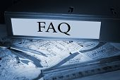 The word faq on blue business binder on a desk