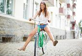 foto of single woman  - Portrait of happy young woman on bicycle  - JPG