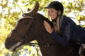 foto of fondling  - Closeup photo of attractive female rider leaning over horse - JPG
