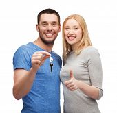 real estate, family, gesture and couple concept - smiling couple holding keys and showing thumbs up
