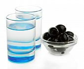 Composition with  two glasses  of vodka, and black olives, isolated on white