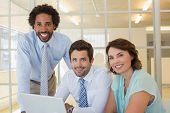 stock photo of half-dressed  - Portrait of three smiling young business people using laptop together at office desk - JPG