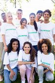 Group portrait of happy multiethnic volunteers together in park