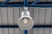 picture of light fixture  - Close up of overhead lighting fixture hanging on factory truss - JPG