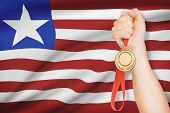 Medal In Hand With Flag On Background - Republic Of Liberia