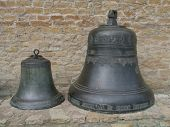 two bronze bells over brick wall