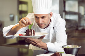 pic of pastry chef  - Closeup of a concentrated male pastry chef decorating dessert in the kitchen - JPG
