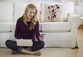 Female In Livingroom With Laptop And Cell Phone poster