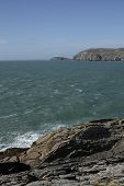picture of anglesey  - A view from rocks across a bay to south stack lighthouse in the distance Wales coast path Anglesey Wales uk.