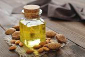 pic of massage oil  - Almond oil in bottle on wooden background  - JPG