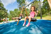 stock photo of swing  - Two beautiful little girls swinging on swings on playground with smile on sunny summer day - JPG