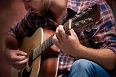 stock photo of fret  - close up of a male musician playing acoustic guitar - JPG