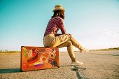 foto of country girl  - Traveler woman sits on retro suitcase and looks away on road - JPG