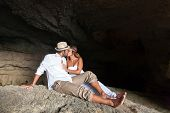 image of cave woman  - portrait of a young couple in love inside a cave of a greek island - JPG