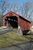 stock photo of mennonite  - The Pool Forge Covered Bridge built in 1859 in Caernarvon Township Lancaster County Pennsylvania crosses the Conestoga River - JPG