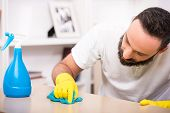foto of cleaning house  - Young man is doing some cleaning work in the house - JPG