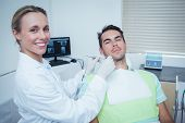 pic of dentist  - Female dentist examining mans teeth in the dentists chair - JPG