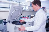 picture of centrifuge  - Chemist in lab coat using a centrifuge in laboratory - JPG
