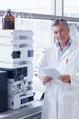 picture of scientist  - Scientist standing in lab coat holding a document in laboratory - JPG