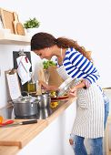 foto of apron  - Beautiful woman standing in kitchen with apron, isolated