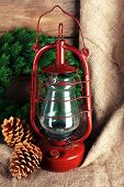 foto of kerosene lamp  - Kerosene lamp with wreath and cones on wooden planks background - JPG