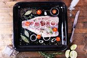 pic of pangasius  - Pangasius fillet with spices and vegetables on firepan and wooden table background - JPG