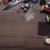 foto of rayon  - needles threads and buttons on brown wooden table in tailor - JPG