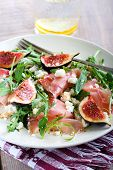 stock photo of rocket salad  - Rocket feta fig and prosciutto salad on plate - JPG