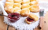 stock photo of buttermilk  - Buttermilk scones with strawberry jam on table - JPG