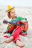 pic of ukulele  - Toned photo of Little happy smiling boy plays his guitar or ukulele - JPG