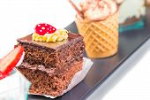 picture of fancy cakes  - delicious chocolate cake in front of little coffee and strawberry cakes on black - JPG