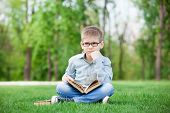 stock photo of sad boy  - portrait of a young sad boy with book on green grass - JPG