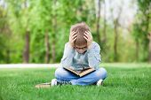 pic of sad boy  - portrait of a young sad boy with book on green grass - JPG