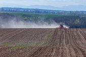 stock photo of cultivator-harrow  - The tractor harrowing the large brown field in spring season - JPG