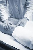 stock photo of injury  - Traumatologist orthopedic surgeon doctor examining middle aged man patient to determine injury pain mobility and to diagnose medical treatment in leg knee meniscus cartilage ankle and foot injury - JPG
