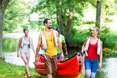 picture of canoe boat man  - Friends carrying kayak or canoe to forest river - JPG