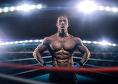 foto of boxing ring  - A strong man in the ring in blue boxing bandages preparing for battle - JPG