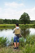 picture of fisherman  - Fisherman on the river bank in sunglasses - JPG