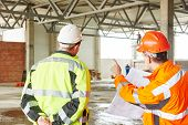 stock photo of engineering construction  - male engineers construction foreman managers outdoors at building site with blueprints - JPG