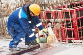 picture of millwright  - Construction builder worker with grinder machine cutting metal reinforcement rebar rods at building site - JPG