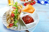 stock photo of tacos  - Tasty taco with nachos chips and tomato dip on table close up - JPG