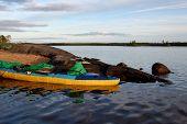 pic of kayak  - Tourist kayak is moored on the bank of the lake agains big stones - JPG