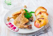 picture of roast duck  - Roasted duck leg with baked apples on white plate - JPG