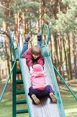 pic of pon  - Sibling children are playing on playground slide made of metal together in old pine park - JPG