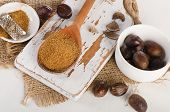 image of ground nut  - Raw Organic ground Nutmeg on white wooden cutting board - JPG