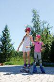 picture of roller-skating  - Two girls skate on roller skates in the park in the summer - JPG