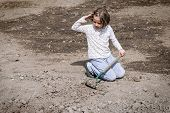 picture of hoe  - Girl digging in dry organic soil by hoe - JPG