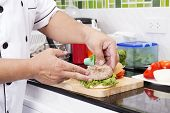 stock photo of hamburger  - Chef putting beef hamburger on the bun  - JPG