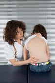 stock photo of scoliosis  - female doctor examines the back of young girl - JPG