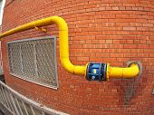 picture of gas-pipes  - Wall of a building with a yellow gas pipe and a large valve with wide angle fisheye view - JPG